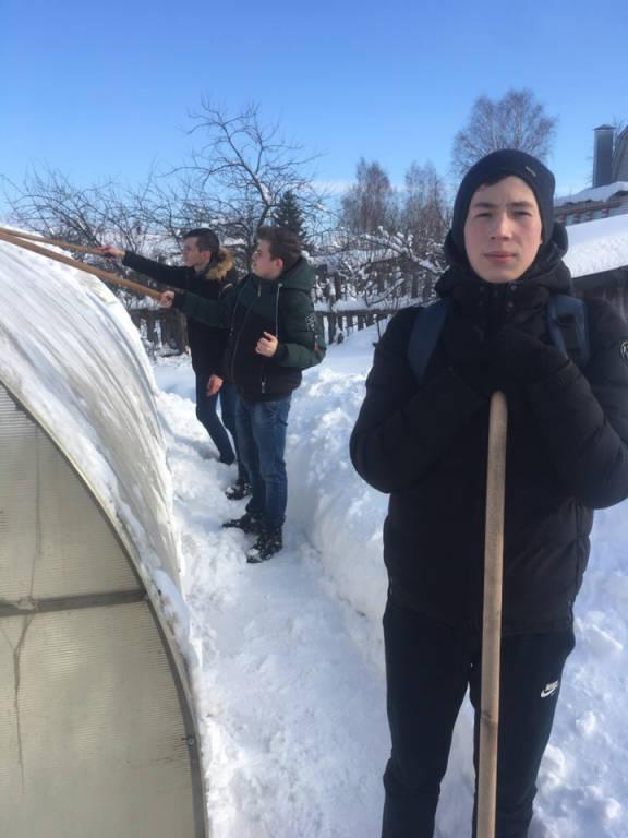 Волонтёры КТВТ помогают жителем города справиться со снегом.